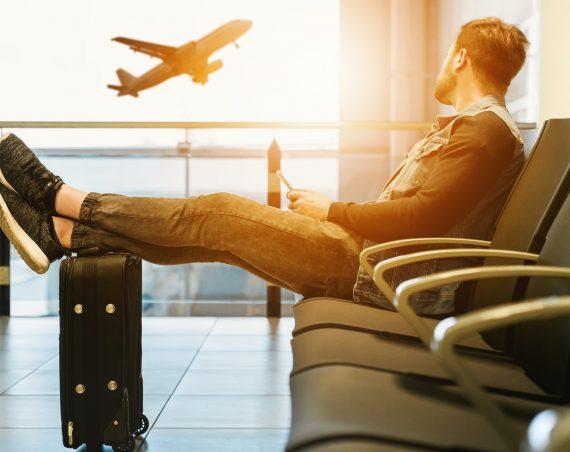 En man kollar på ett flygplan som lyfter