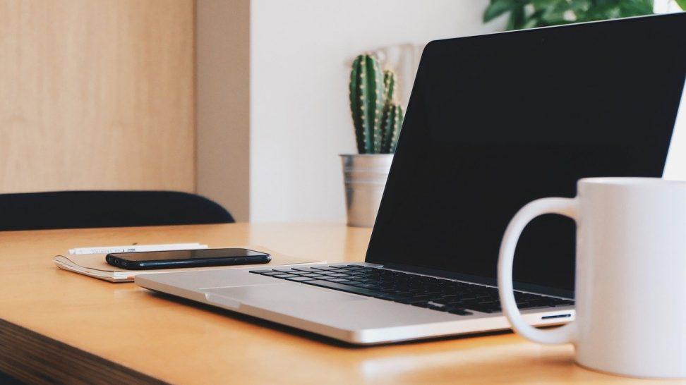 En laptop och en telefon på ett skrivbord
